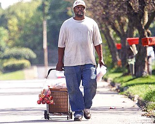 "Darren Moore of Cohasset Drive walks home with his shopping cart full of fresh food and drinks from Jordan's Market on Market Street on Youngstown's South Side. The city is rated as the third worst urban ""food desert'' in the U.S."