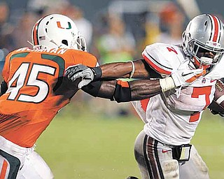 Ohio State running back Jordan Hall (7) runs as Miami linebacker Ramon Buchanan (45) defends during the second quarter of an NCAA college football game in Miami, Saturday, Sept. 17, 2011. (AP Photo/Lynne Sladky)