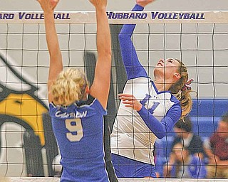 (11) Maris Sarisky of Hubbard goes up for the spike as (9) Calli Schmitt tries for the block Monday evening.