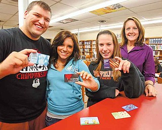 From left, Springfield High School senior Stephen Lyons, junior Shelby Romanchuk, senior Lexy Zubic and school librarian Amy Crowe show off the students' new library cards. Students will use the public library instead of school computers to access academic databases — saving the district about $5,000 annually.
