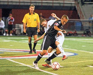Austintown Fitch senior Mike Shaffer, white uniform, battles for possession against Canfield senior Tony ElHayek during the first half of Thursday's boys soccer game in Austintown. The Cardinals won the AAC contest, 2-1.
