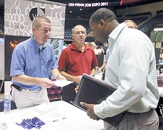 Kevin Young, left, a maintenance supervisor for V&M Star, speaks with Michael Cook, 37, of Youngstown about job opportunities at the company at the sixth annual Ohio-Penn Interstate Job Expo at the Covelli Centre.
