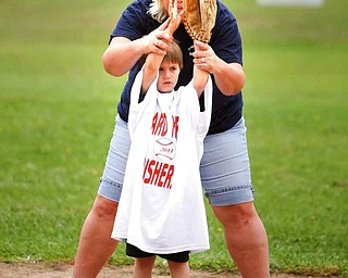 Cherie O'Neill gives Logan Halk, 6, of Struthers, some pointers. The game was at the Poland Community Baseball Association North Field Complex.