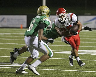 JESSICA M. KANALAS | THE VINDICATOR ..Ursuline's defensive back's Shannon Hightower, 6, and Deon Jackson, 30, tackle Steubenville's player during the second quarter of Friday night's game at YSU stadium.  ..-30
