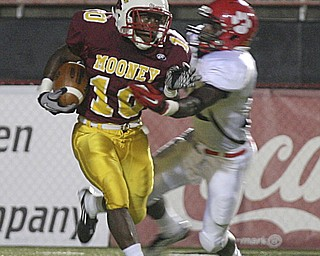 JESSICA M. KANALAS | THE VINDICATOR ..Mooney's junior running back Justus Ellis-Moore avoids a tackle from junior defensive back Quashawn Lister of the Red Lion Christian Academy during the first quarter of Saturday night's game at YSU stadium. ..-30