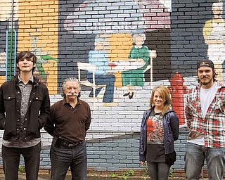 Three Youngstown State University seniors are refurbishing a mural on the side of a building adjacent to Avalon Gardens on Belmont Avenue. Avalon owner Jim Donofrio, second from left, wanted to revive the artwork and asked the students, from left, Evan James of Boardman, Valerie Nichols of Austintown and Derek Dickey of Canfield, for their expertise.