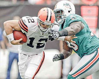 Miami Dolphins defensive end Kendall Langford, right, pressures Cleveland Browns quarterback Colt McCoy in the first quarter in an NFL football game on Sunday, Sept. 25, 2011, in Cleveland.  (AP Photo/Mark Duncan)