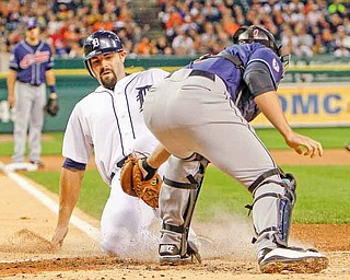 Detroit Tigers' Alex Avila safely slides under the tag of Cleveland Indians catcher Lou Marson on teammate Ryan Raburn's triple during the second inning of a baseball game, Monday, Sept. 26, 2011, in Detroit. (AP Photo/Carlos Osorio)