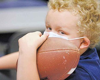 Mickey Howard, 6, a patient at Akron Children's Hospital Mahoning Valley, waits to have his football autographed by Jim Harbaugh, head coach of the 49ers. Harbaugh and several players visited the hospital Monday.