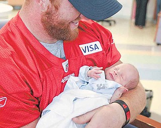 The 49ers' Bruce Miller holds 3-week-old Michael McCall, who was born 32 weeks premature.
