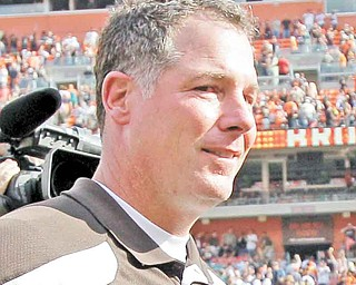 Cleveland Browns coach Pat Shurmur walks off the field with a game ball after the Browns beat the Miami Dolphins 17-16 in an NFL football game Sunday, Sept. 25, 2011, in Cleveland.  (AP Photo/Amy Sancetta)