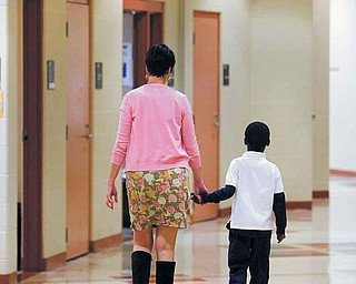 A teacher at Taft Elementary School in Youngstown accompanies a student down the hall. Taft administrators say students need to know that the school is a safe place and that someone there cares about them.