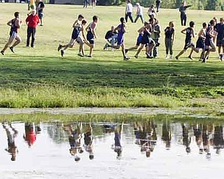 Runners are refl ected in Yeager's Pond during Tuesday's Mahoning County boys cross country meet at Austintown Park.