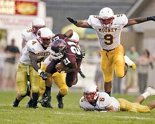 Boardman's Devin Campbell (21) eludes Cardinal Mooney defenders Marcus McWilson (4), Joe DeNiro (6) and Courtney Love (9) during Week 2 action in Boardman.