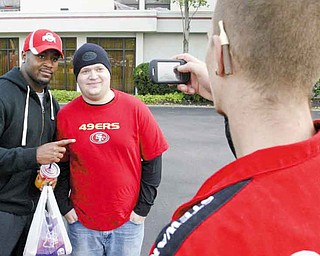 Donte Whitner of the San Francisco 49ers poses with fan Andrew Berg of Bessemer, Pa., while Alex Reece of Boardman snaps a photo outside the Holiday Inn in Boardman. The team has been in the area since Monday.