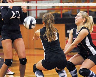 Girard's Kara Miller (22) watches as Amy Jackson (13) and Katanna Austolosh (6) of Campbell Memorial set the ball during their All-American League volleyball match Thursday at Campbell Fieldhouse. The Indians defeated the Red Devils, 3-0.