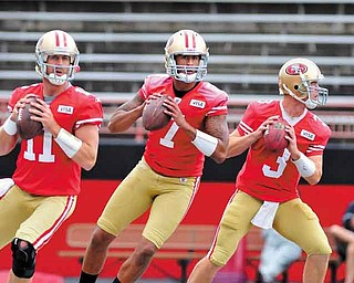 Quarterbacks Alex Smith #11, Colin Kaepernick #7 and Scott Tolzien #3 drop back to pass during a passing drill Thursday at Stambaugh Stadium.
