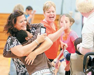 Joy DeCapita, substitute aide for Leonard Kirtz School, hugs Emani Martinez, 11, as they dance to Lady Gaga music during the school's Harvest Carnival on Friday. More than 150 students and clients from the school and Bev Road and Meshel MASCO workshops attended the event.