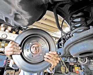 Bob Little, CEO of Ed Little Auto Service in Culver City, California, handles the rotor of a car receiving a brake job at his car repair shop on August 22, 2011. Many auto repair shops are flourishing in tough economic times for many Americans, according to industry statistics. (Mel Melcon/Los Angeles Times/MCT)
