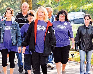 Johanna Morell Nuzzo, front, and her team cross the finish line together at Saturday's Walk to End Alzheimer's event. The event, which raised more than $35,000, was at Boardman Park.
