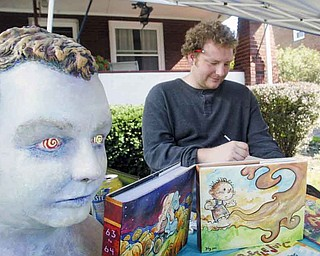 Jimmy Proctor, an artist from Springboro, Pa., creates custom covers for books. He was at Lawn-Con, a free comic book show, which took place Saturday in the Hartford Avenue front yard of local artist Chris Yambar.