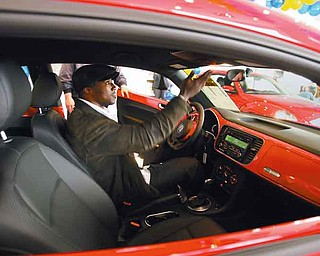 """Deryck Toles of Warren checks out the 2012 Volkswagen Beetle 2.5L he picked up at Stadium Volkswagen in Boardman. He and Kimberly Winfrey of Warren were two of 275 audience members who received the prize during Oprah Winfrey's """"Ultimate Favorite Things"""" episode that aired in November 2010."""