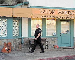 A Seal Beach police officer walks in front  of the site where eight people were killed and one was wounded Wednesday in a shooting at Salon Meritage in Seal Beach, Calif., Thursday, Oct. 13, 2011. (AP Photo/Chris Carlson)