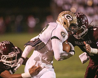 ROBERT  K.  YOSAY  | THE VINDICATOR --..It takes two as Boardmans #21 Devin Campbell and Bdm #1 Dayne Hammond  Stops Glenoak #7  Dashawn Hall  during first half action -.Glen Oak vs Boardman at Boardman High School -..--30-..(AP Photo/The Vindicator, Robert K. Yosay)