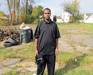 Roderick Lewis Jr. of Warren stands on the edge of a run-down park on Burton Street Southeast where he and others have been  working recently to clean up. Lewis, 21, has been donating hundreds of dollars each year to a school-supplies giveaway and been involved in other community projects.