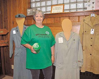 Trudee Davis of Austintown is historian of the Eastern Region of the Girl Scouts of North East Ohio. She's displaying some of the Girl Scout uniforms she has collected, including ones from 1928 and 1919 at her left.