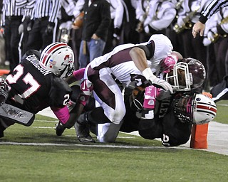 Boardman's Devin Campbell reaches for the endzone while being tackled by McKinley's #27 Jermaine Edmondson and #20 Chad Fite.