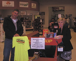 """'Spread the Cheer': Witmer's Inc., 39821 Salem Unity Road, Salem, has started its third annual """"Spread the Cheer"""" food drive. Kicking off this year's drive are Nelson Witmer and Grace Styer, above. The goal is to fill the Pequea 80-bushel manure spreader as many times as possible for Thanksgiving and then again for Christmas. Anyone who takes in at least six nonperishable food items or six household items, such as paper towels, toilet tissue or soap, etc., will receive a Witmer's T-shirt while supplies last. Limit one shirt per person per visit. This will help replenish the shelves of several local food banks."""