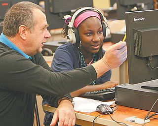Gerald Wansack, a tutor at P. Ross Berry Eighth and Ninth Grade Academy in Youngstown, helps Johntaesia Allen, an eighth-grader, work through an algebra problem using a computer program.