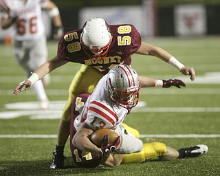 ROBERT  K.  YOSAY  | THE VINDICATOR --..STOPPED as Indians #13  J C Pawlyk is stopped and brought down hard by #14  Ryan Farragher ( hidden) and #58  Brian Zordich during second quarter action ..Cardinal Mooney Cardinals vs Canal Fulton Northwest Indians at Stambaugh Stadium in the Regional Quarterfinals .--30-..(AP Photo/The Vindicator, Robert K. Yosay)
