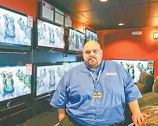 Mark Worsencraf, the general manager of Aron's Sales and Services, stands by a row of LCD TVs. Since opening in the Austintown Plaza in June, the retail store has donated $5,000 to local charities and community groups.