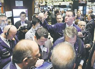 Trader Jonathan Corpina, right center, works on the fl oor of the New York Stock Exchange on Wednesday. The Dow Jones industrial average plunged 389 points Wednesday after Italy's borrowing costs soared, a sign that Europe's debt crisis had spilled into the third-largest economy in the euro bloc.
