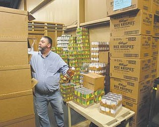Pastor Joseph Delapa of High Pointe Church in Lowellville sorts through supplies for the free Thanksgiving dinner the church will sponsor Nov. 17 at Struthers High School. It's the 14th such event for the Assembly of God congregation and is among a host of such dinners in the Valley.
