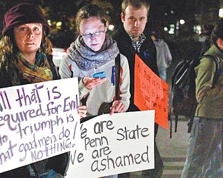 Penn State students stand outside the Old Main building on campus in State College, Pa., on Wednesday protesting the handling of a child abuse scandal involving retired Penn State assistant football coach Jerry Sandusky. PSU trustees fired head football coach Joe Paterno and university president Graham Spanier because they didn't do enough to alert law enforcement authorities.