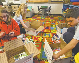St. Joseph and Immaculate Heart of Mary sixth-graders Meg Welsh, left, Katie McHugh and Joey Jadue pack boxes with candy and supplies in honor of Veterans Day. Members of the school's student council will send the care packages to soldiers overseas.