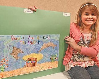 Hilltop Elementary School student Briana Maurer proudly displays the poster she created for the Mahoning County Juvenile Court Advisory Board's eighth annual school poster contest. Briana won second place in the third-grade county category.