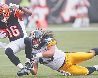 Bengals wide receiver Andrew Hawkins (16) is tackled by Steelers safety Troy Polamalu (43) in the second half of Sunday's game in Cincinnati.