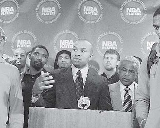 Surrounded by NBA players, including New York Knicks' Chauncy Billups, left, and Oklahoma City Thunder's Russell Westbrook, right, NBA Players Association president Derek Fisher speaks during a news conference after a meeting of the players' union in New York Monday.