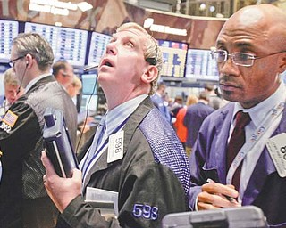 Traders Richard Cohen, left, and Lewis Vande-Pallen, work on the floor of the New York Stock Exchange on Monday. The Dow Jones industrial average took a fall of nearly 250 points Monday in reaction to the
