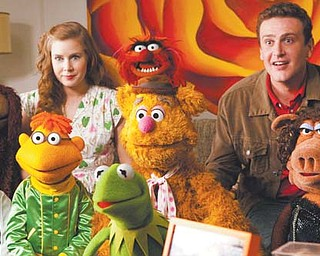 "Amy Adams, left, and Jason Segel are shown with the Muppet characters in a scene from ""The Muppets."""