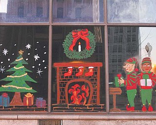 The reflection of First National Bank tower in downtown Youngstown looms in the background of this holiday scene painted on Chase Bank windows on West Federal Street by Youngstown State University Art Association students.