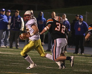 FOOTBALL - (15) P.J. Quinn scrambles away from (32) Jack Campbell Friday night in Uniontown. - Special to The Vindicator/Nick Mays