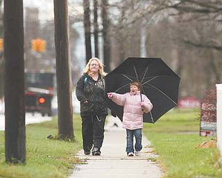 Diane Wagner and Judy Peyatt, her 7-year-old daughter, both of Niles, walk home together in the rain after school on Robbins Avenue. With a month to go, 2011 is already the area's second-wettest year on record.