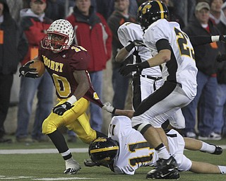 Mooney #10  Justus-Ellis Moore is tackled by #11 Shawnee Grant Miller and #23 Drew Young by his shirt. Youngstown Cardinal Mooney won their 8th championship as they beat the Shawnee Braves in Fawcett Stadium  21-14. (AP Photo/The Vindicator, Robert K. Yosay)