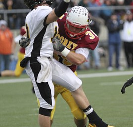 Mooney #35 Anthony Dermotta dislodges the QB for Shawnee Brad Jarzab during second half action. Youngstown Cardinal Mooney won their 8th championship as they beat the Shawnee Braves in Fawcett Stadium  21-14. (AP Photo/The Vindicator, Robert K. Yosay)