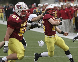 Shawnee #14 Dusty Seelig gets the facemask of PJ Quin as #51 Carmen Lanzo -  they scored on the next play. Youngstown Cardinal Mooney won their 8th championship as they beat  the Shawnee Braves in Fawcett Stadium  21-14. AP Photo/The Vindicator, Robert K. Yosay)